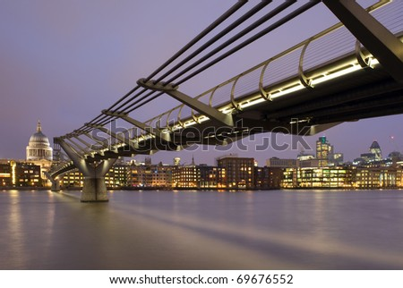 St. Paul's Cathedral and the Millennium Bridge at night in London, England. - stock photo