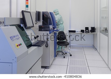 "ST. PETERSBURG, RUSSIA - APRIL 18, 2016: Man in cleanroom suite working in clean room at JSC ""Avangard"". It is Russia's leading company in radio electronics and microsystems engineering - stock photo"