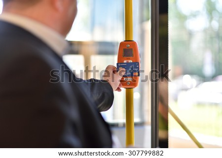 ST. PETERSBURG, RUSSIA - AUGUST 17, 2015: Deputy General Director of Information Networks LTD Kirill Petrenko demonstrate the PayPass technology in transport ticketing system in the line 5 trolleybus - stock photo