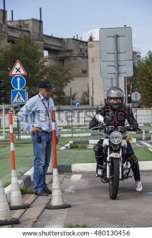 ST. PETERSBURG, RUSSIA - CIRCA AUG, 2016: Woman motorcyclist listens the instructor before exercise of driving bike into parking lot. Skill training motordrome. Russian driver school
