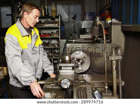 St. Petersburg, Russia - 22 December 2011: Turner grinds steel part on a lathe.