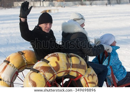 St. Petersburg, Russia - February 11, 2015: Happy smiling family is riding a snowmobile on a sunny winter day in the countryside.