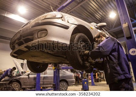 St. Petersburg, Russia - February 8, 2012: mechanic repairing a vehicle chassis raised on the stocks in the garage - stock photo