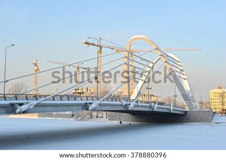 St. Petersburg, Russia - January 22, 2016: winter views of construction cranes and Lazarevsky bridge across the Small Nevka River. New bridge was built in 2009 instead of old wooden bridge - stock photo