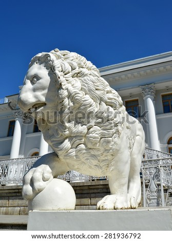 ST. PETERSBURG, RUSSIA - JULY 11, 2014: A white stone lion with a sphere against Yelagin Palace - stock photo