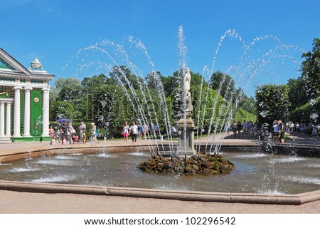 ST. PETERSBURG, RUSSIA - JULY 02: Tourists visiting the sights of the lower park of Peterhof (after the solemn opening of the fountains) on July 02, 2011 in St. Petersburg, Russia. - stock photo