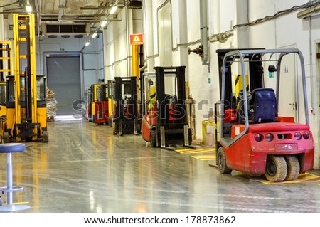 ST-PETERSBURG, RUSSIA - JUNE 13, 2013: Interior Storage terminal with loaders, standing along the walls. Corridor large warehouse. Forklift Trucks in stock.