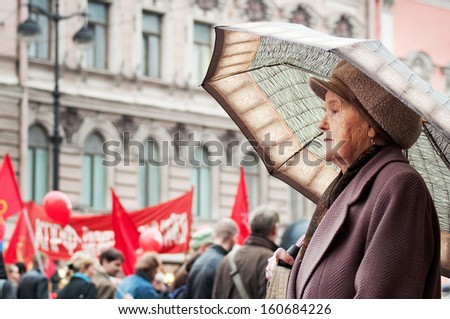 St. Petersburg, Russia - May 1: An old woman looks at the May Day Communist demonstration on May 1, 2010 in St. Petersburg, Russia