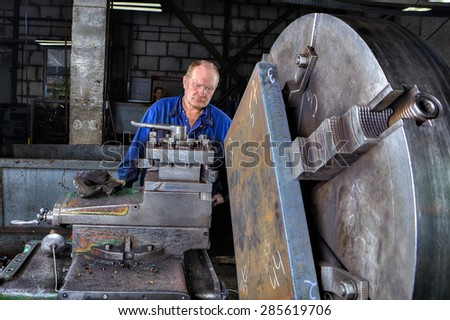 St. Petersburg, Russia - May 21, 2015: Machine tool operator handles steel billet clamped in a large jaw chuck, big lathe in the factory of metal constructions.
