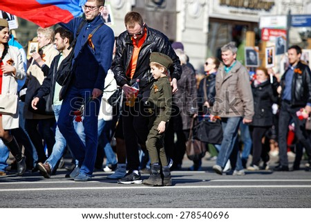 "ST.PETERSBURG, RUSSIA: - MAY 9, 2015: The father offers water to the son dressed in a form of the Soviet soldier. The action ""immortal regiment"" in honor of a Victory Day of the Soviet Union - stock photo"