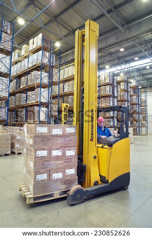 St. Petersburg, Russia - November 21, 2008: The driver of a yellow forklift truck operates, in warehouses, sitting in the workplace. A fork lift truck moves stacked pallets. Forklift palletiser. - stock photo