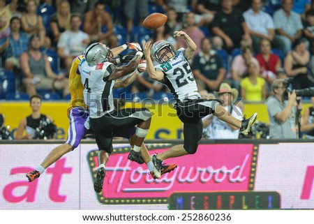 ST. POELTEN, AUSTRIA - JULY 27 DB Andreas Bertsch (#25 Raiders), DB Talib Wise (#4 Raiders) and WR Stefan Holzinger (#17 Vikings) fight for the ball at Austrian Bowl XXVII. - stock photo