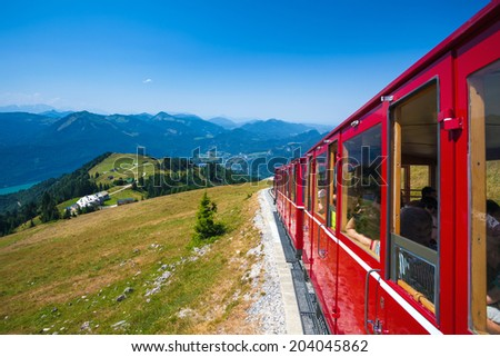 ST. WOLFGANG, AUSTRIA - AUGUST 6: Steam locomotive of a vintage cogwheel railway going to Schafberg Peak (1783m) on August 6, 2013 in St. Wolfgang. - stock photo