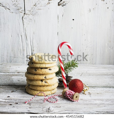 Stack of American cookies with Christmas toys and spruce branches, sweet staff on a simple white wooden background. Christmas holiday card - stock photo