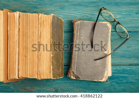 Stack of antique books and glasses on blue wooden background - stock photo