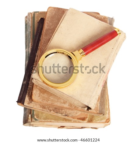 Stack of antique books and magnifying glass - stock photo