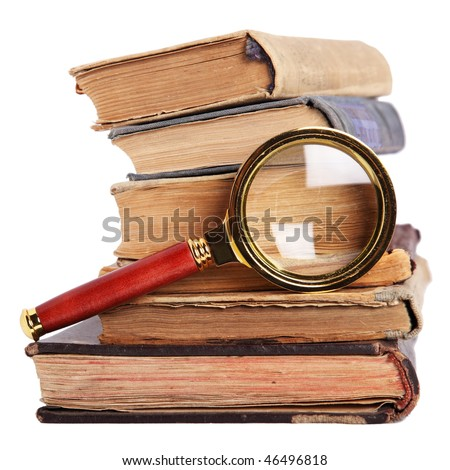 Stack of antique books and magnifying glass isolated on white - stock photo