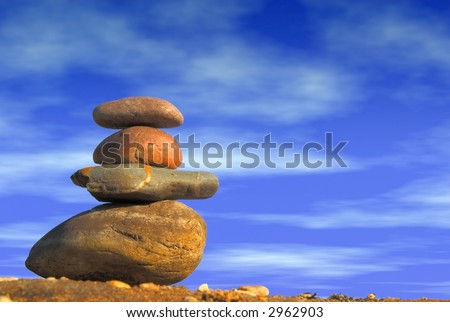 Stack of balanced pebbles, stones against colorful  blue cloudy sky. Zen, meditation, inner peace concept. Copy space. - stock photo