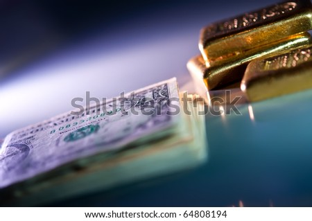 stack of banknotes and gold bars on blue and purple background - stock photo