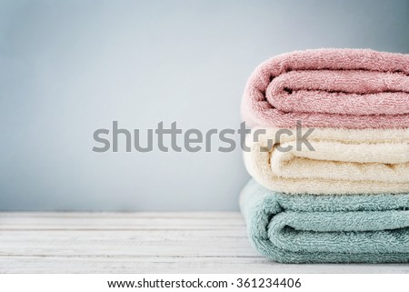 Stack of bath towels on light wooden background closeup - stock photo