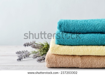 Stack of bath towels with lavender flowers on light wooden background closeup - stock photo