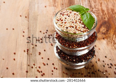 Stack of bawls with red, black and mixed raw quinoa, South American grain with basil leaves on old rustic wooden background. Top view. Background with copy space. - stock photo