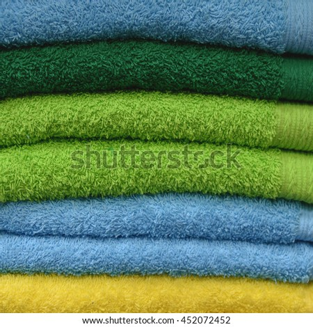 Stack of beautiful colored bath towels in a green, blue, yellow color. Close up. Everyday care about your body. Everything for your hygiene. Pile of nice fluffy and soft towels. Domestic objects  - stock photo