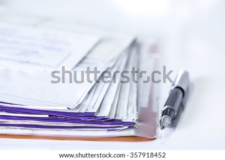 Stack of bills and pen - stock photo