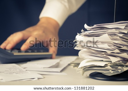 Stack of bills in paper nail with hand calculating - stock photo