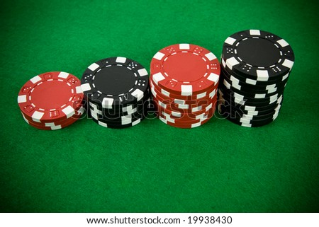 Stack of black and red poker chips on green table.
