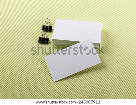 Stack of blank business cards on a green background. Template for branding identity. - stock photo