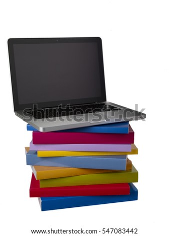 Stack of blank colorful books with slim laptop sitting on top
