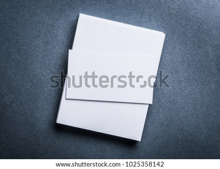 Stack of blank white business card on grey textured background top view. Identify design, corporate templates.