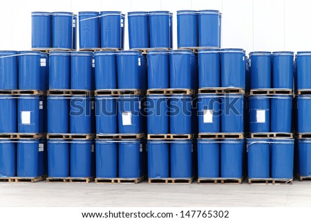 Stack of blue barrels in chemical factory - stock photo