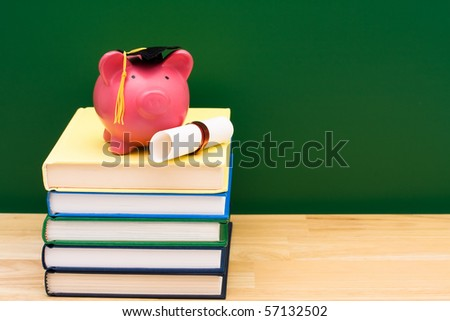 Stack of blue books with a piggy bank in front of a chalkboard, Costs of an education - stock photo