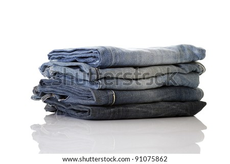 Stack of blue jeans on a white background, perfect reflection - stock photo