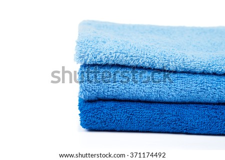 Stack of blue terry towels isolated on white - stock photo