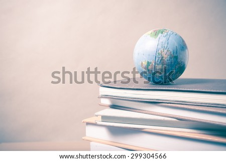 stack of book and earth ball on wood background vintage style - stock photo