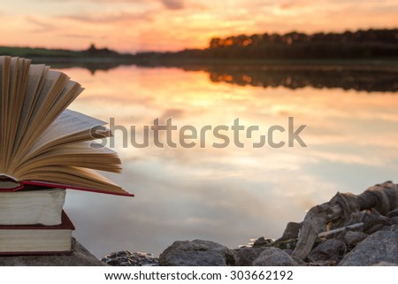 Stack of  book and Open hardback book on blurred nature landscape backdrop against sunset sky with back light. Copy space, back to school. Education background. - stock photo