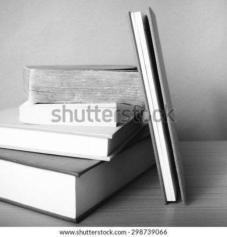 stack of book on wood table background black and white color tone style