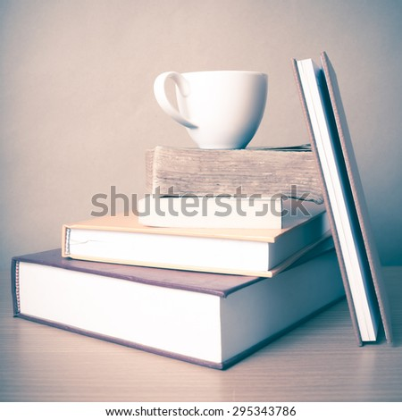 stack of book with coffee cup on wood table background vintage style