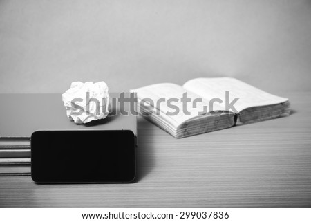 stack of book with smart phone on wood background black and white color tone style