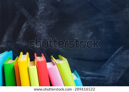 stack of books against the background of the teachers' board