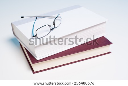 Stack of books and a pair of reading glasses on white background - stock photo