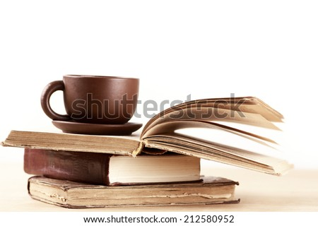 Stack of books and cup on wooden table. Shallow DOF. - stock photo