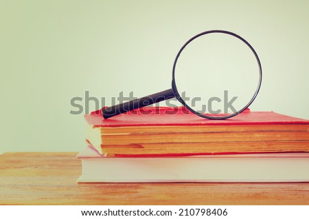 stack of books and magnifying glass. room for text. image is retro filtered.  - stock photo