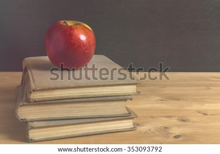 Stack of books and red apple on wooden table. Selective focus.