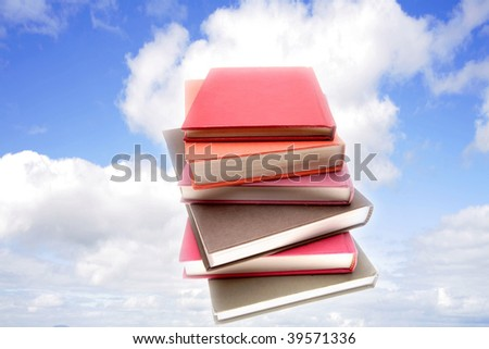 Stack of books in blue sky. - stock photo