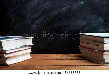 stack of books in front of the black board - stock photo