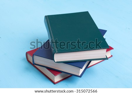 stack of books on a blue wooden background - stock photo